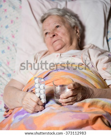 Old sick woman lying at bed, going to take the medicine at home - stock photo