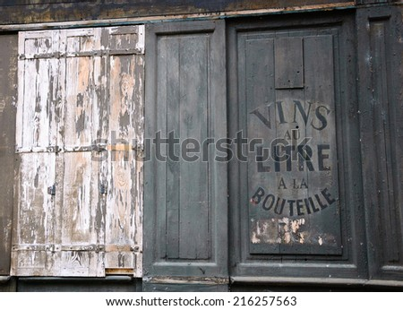 "Old sign outside abandoned wine and spirit  store. Text in French ""Vins au litre, a la bouteille"" meaning ""Wine selling by liters or in bottles"".  - stock photo"