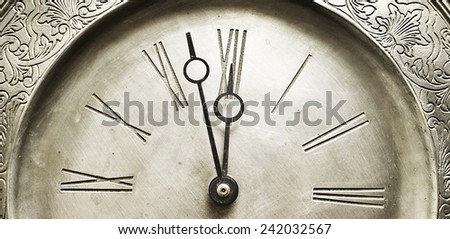 Old silver clock with roman numbers indicating it's about time. - stock photo