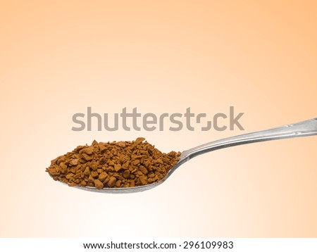 Old silver teaspoon with granulated instant coffee isolated on brown - stock photo