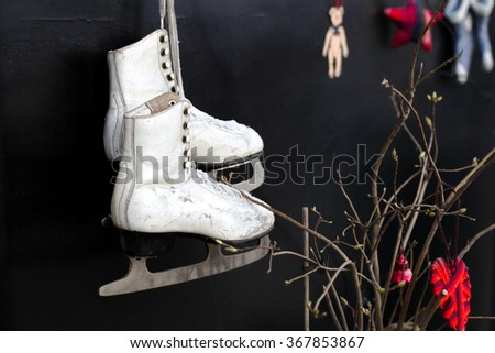 old skates hanging on the laces on a black background - stock photo