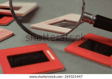old slides and a magnifying glass on green table. Toned - stock photo