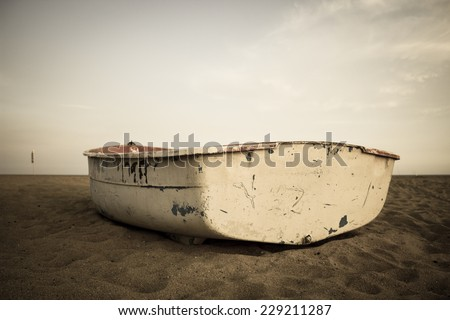 Old small composite fishing boat on the beach and sky up the horison in sepia - stock photo