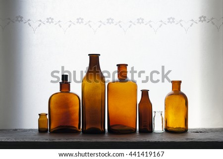 Old small glass bottles in row at windowsill against daylight - stock photo