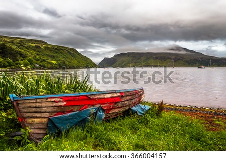 Old small rowing boat with its color peeling off on the shore of a scottish bay with green hills and dramatic clouds in the background - stock photo