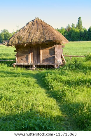 Old small rural house with a straw roof - stock photo