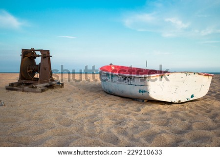 Old small white and red composite fishing boat on the beach and blue sky up the horison - stock photo