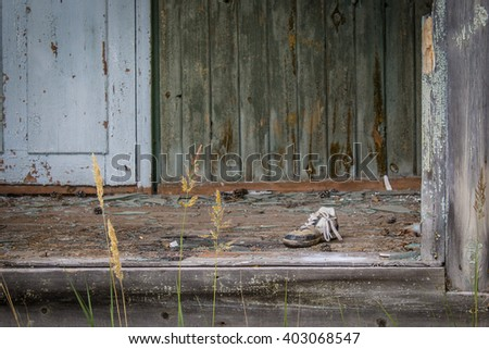Old sneaker on an abandoned house threshold - stock photo
