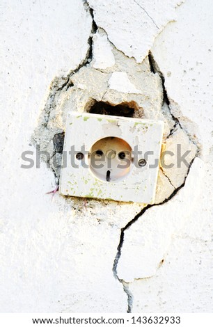 Old socket on a cracked white wall - stock photo