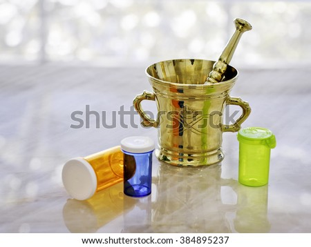 Old solid brass mortar and pestle with colorful pill containers  - stock photo