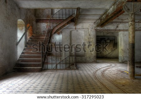 Old staircase in an abandoned factory and tracks - stock photo