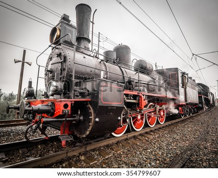 Old steam engine locomotive with puffs of white steam passes a turn on the railroad - stock photo