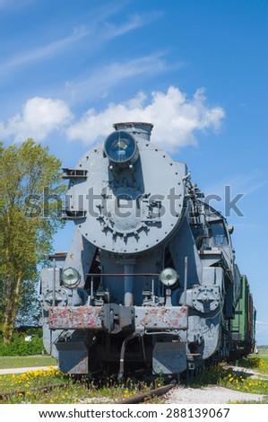 Old steam locomotive train under blue sky - stock photo