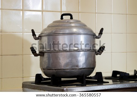 Old steamer pot on the stove in the kitchen - stock photo