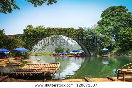 old stone arch bridge in yulong river ,yangshuo,China. - stock photo