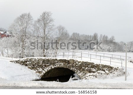 "Old stone bridge, called ""Hamar Bridge"" in Lørenskog, near Oslo, Norway. The bridge and the trees are covered by fluffy snow, making an idyllic scene. - stock photo"