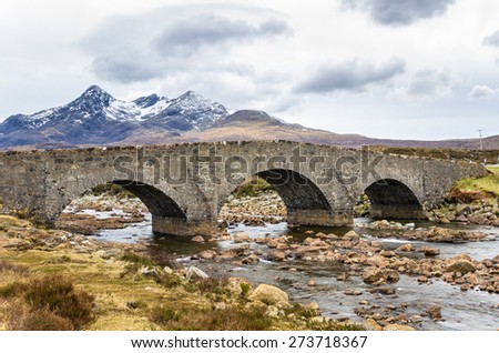 Old Stone Bridge over the River Slichagan with Mountains in Background, Isle of Skye, Scotland - stock photo