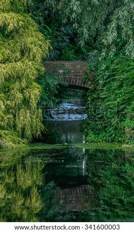 Old stone bridge spanning a moat near Bergambacht, The Netherlands - stock photo