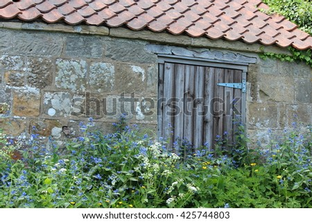 Old Stone Building Overgrown With Flowers, Yorkshire. - stock photo