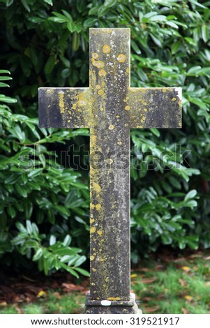 old stone cross in church grounds surrounded by bushes - stock photo