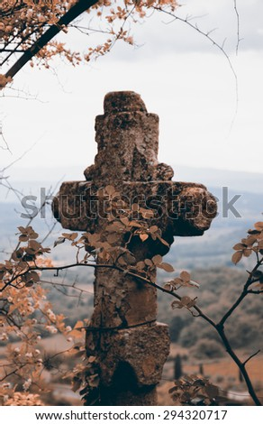 Old stone cross over the valley. Religion background. Retro aged photo. Selective focus on the leaves. - stock photo