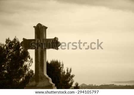 Old stone cross with star over the valley. Religion background. Aged photo. Sepia. - stock photo