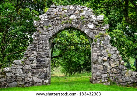 Old stone entrance wall in green landscaped garden - stock photo