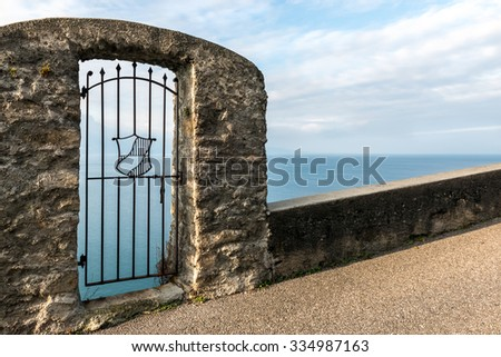 Old stone fence and metal gate above the blue lake. Vineyard terrace in Lavaux, Switzerland. - stock photo