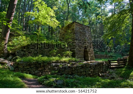 Old stone furnace in woods. - stock photo