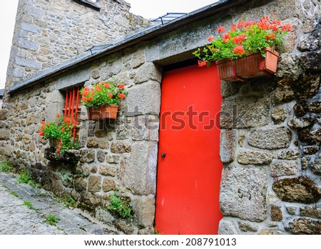 Old stone house with red door, red painted grilles on the windows and hanging boxes with red geranium flowers. Medieval town Moncontour. Brittany, France - stock photo