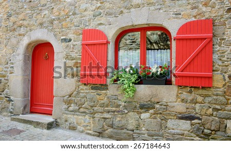 Old stone house with red wooden shutters and red door. Boxes with red and white flowers on the window. Brittany, France - stock photo