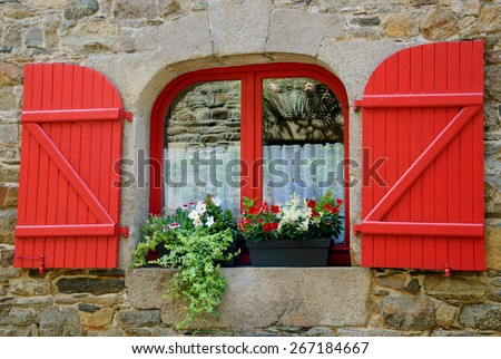 Old stone house with red wooden shutters. Boxes with red and white flowers on the window. Brittany, France - stock photo