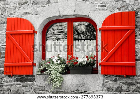 Old stone house with red wooden shutters. Boxes with red and white flowers on the window. Brittany, France. Retro aged photo. - stock photo