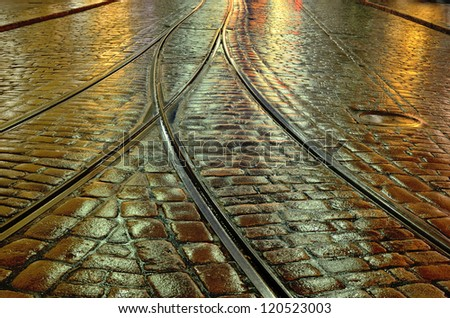 old stone pavement and the tram rails - stock photo