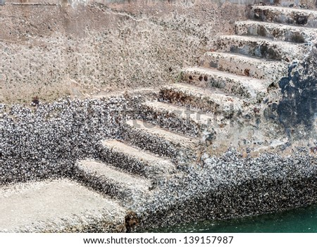 Old stone staircase in front of the travel boat pier. - stock photo