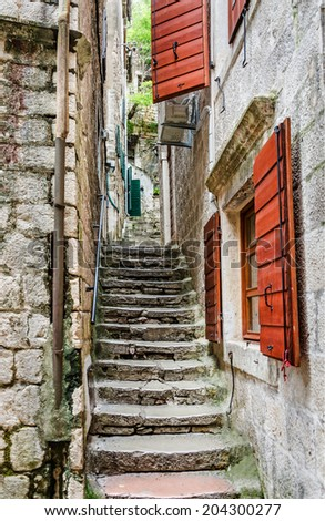 Old stone stairs through a narrow alley with red shutters in the old town of Kotor, one of the most famous places on Adriatic coast of Montenegro. - stock photo