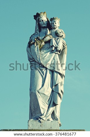 Old stone statue of the Virgin on tomb and Jesus Christ Crowned at the cemetery in Ukraine in vintage style - stock photo