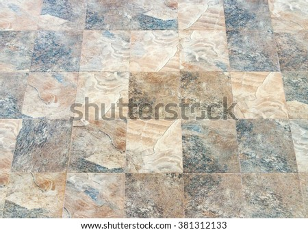 Old stone tile on the footpath in town. - stock photo