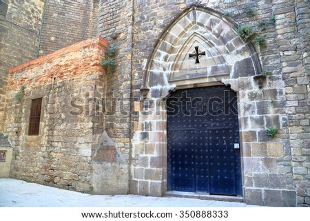 Old stone wall and church door from Barri Gothic quarter in Barcelona, Catalonia, Spain - stock photo