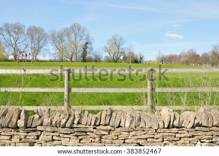 Old Stone Wall and Wooden Fence on Farmland - stock photo