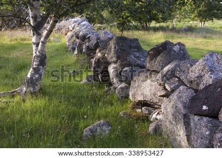 Old stone wall at Blomsoy, Helgeland archipelago, Norway - stock photo
