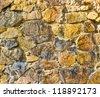 Old stone wall in yellow tone - stock photo