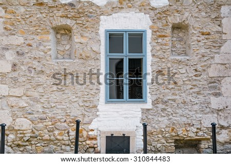 Old Stone Wall of Medieval House with Closed Window - stock photo