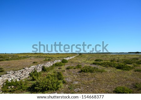 Old stonewall through a great plain area on the island Oland in sweden - stock photo