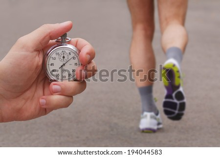 Old stopwatch in a hand and blurred runner athlete feet running on a road - stock photo