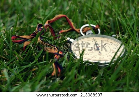 Old stopwatch in the green grass - stock photo