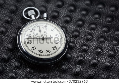 Old stopwatch lying on dark leather. Made of silver chromed metal. Macro photo. - stock photo