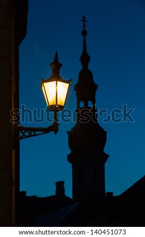 Old street lamp and church silhouette at night. Old town of Tallinn, Estonia - stock photo