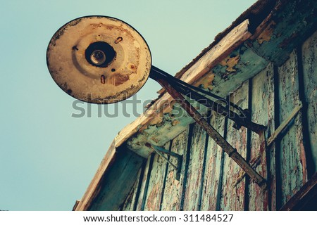 Old street lamp on roof. Toned image.  - stock photo