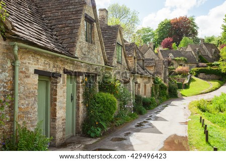 Old street with traditional cottages in  beautiful spring day , Bibury, England, UK. - stock photo